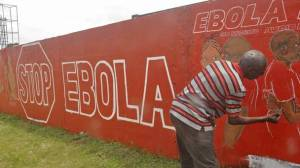 A local Liberian artist paints a mural forming part of the country's fight against the deadly Ebola virus (AP)